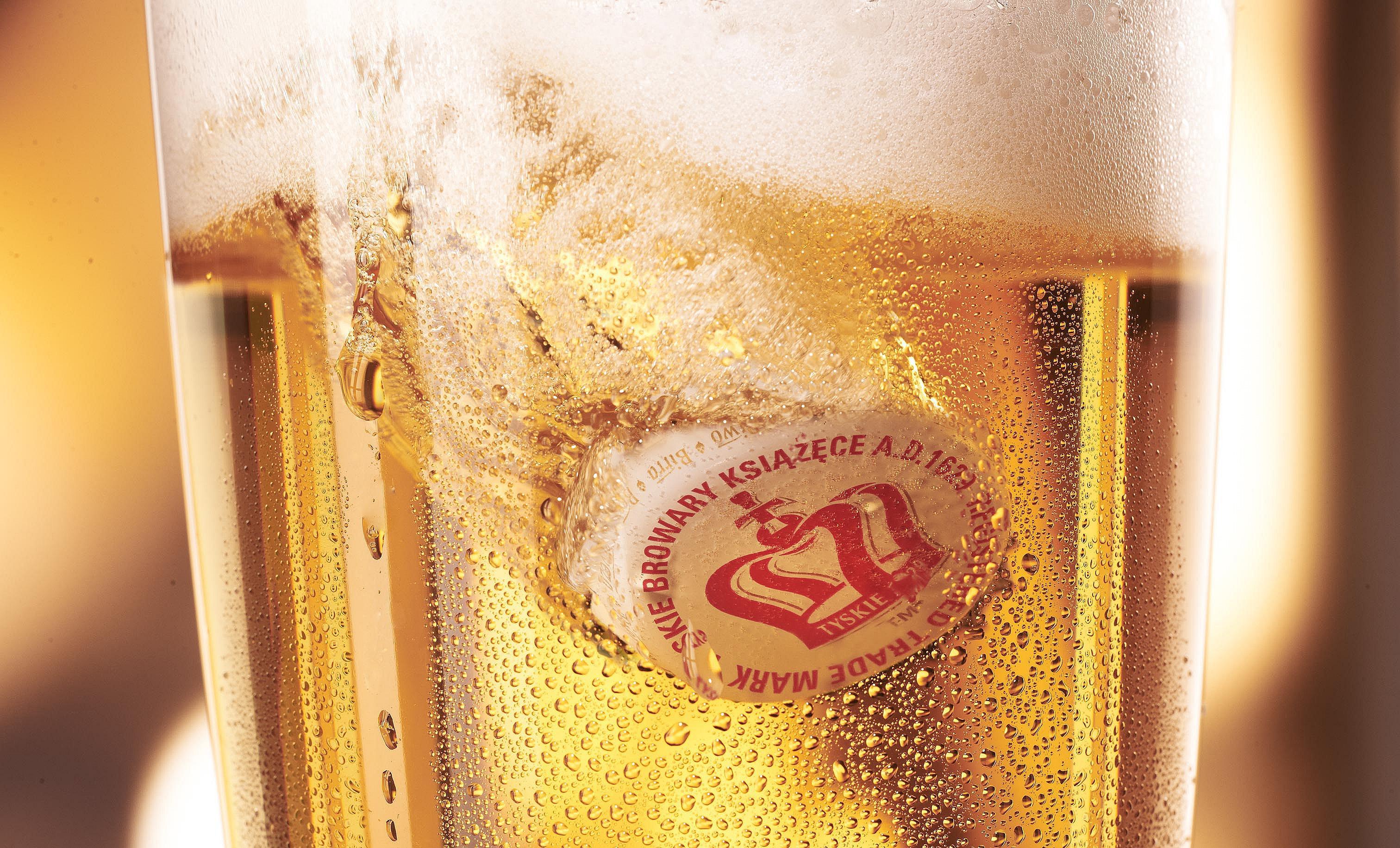 Kronkorken taucht in ein Bierglas ein