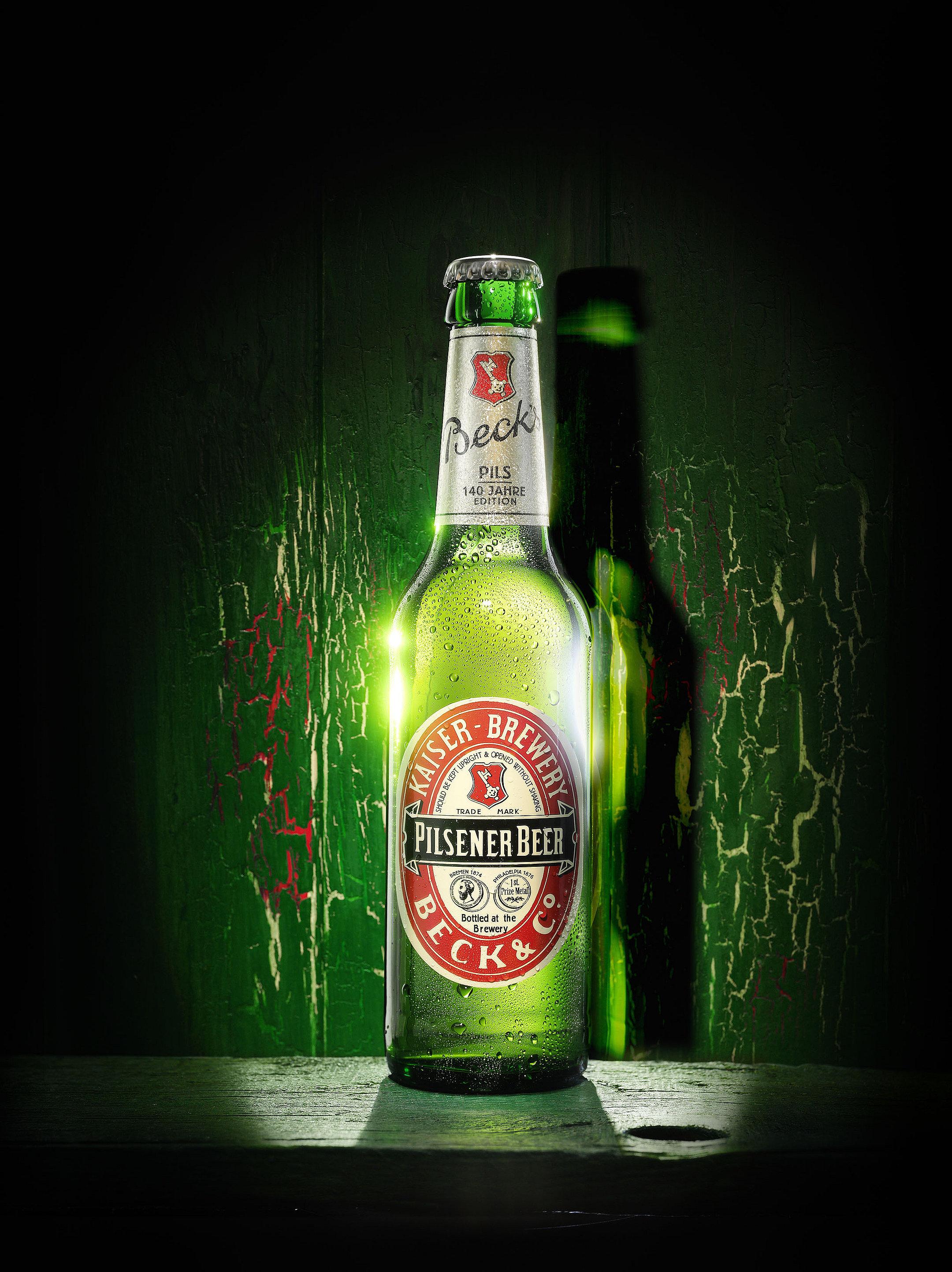 leuchtende Becksbierflasche vor grünem Holz Hintergrund
