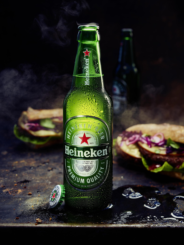 Geöffnete Heineken Pils Flasche gekühlt mit Sandwiches/Burger im Hintergrund