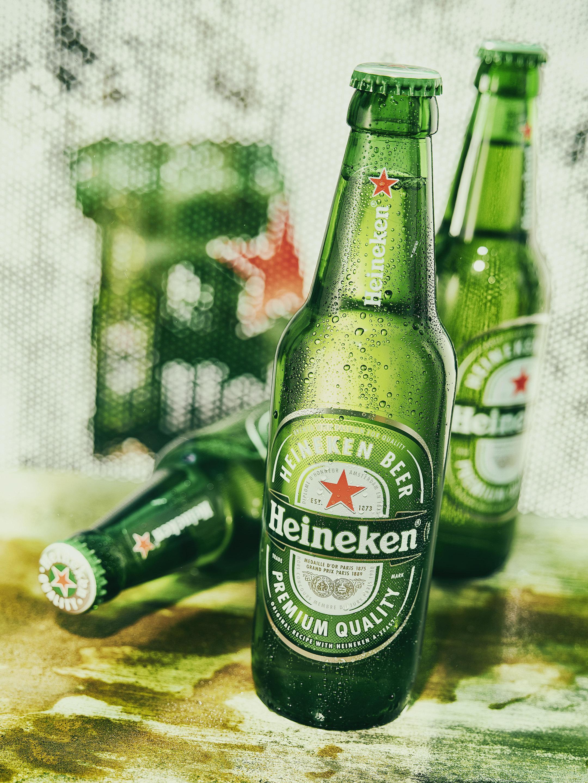 Verschiedene geschlossene und gekühlte Heineken Pilsner Flaschen vor gerastertem Hintergrund