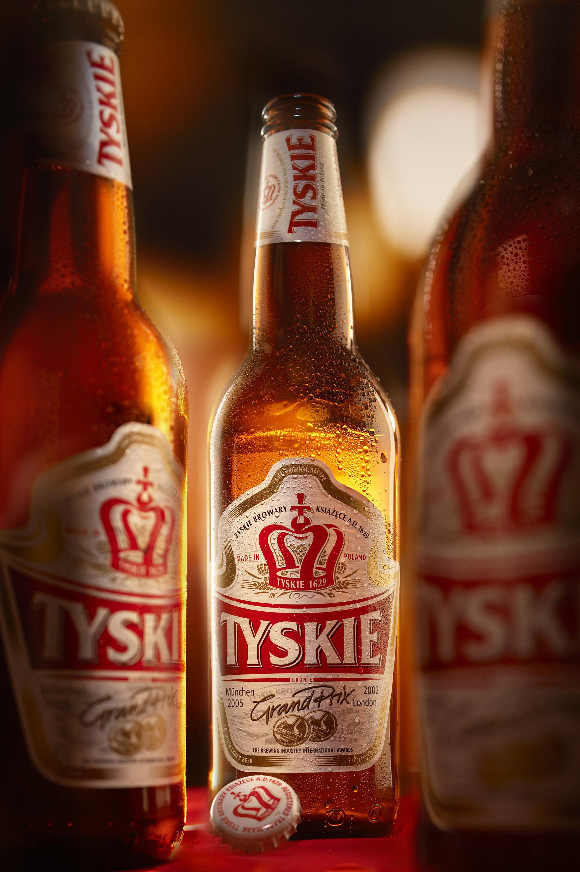 Mehrere Tyskie Bierflaschen scharf/unscharf geöffnet und gekühlt mit nebenliegenden Kronkorken